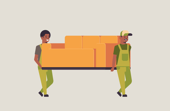 two african american couriers in uniform moving couch express delivery service concept professional furniture movers holding new sofa flat full length horizontal