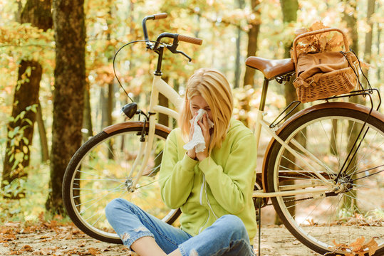 Runny nose remedies. Seasonal allergy. Woman handkerchief sneezing because of allergy. Blonde allergic reaction relax forest. Girl bicycle in nature. Woman bicycle autumn forest suffers from allergy