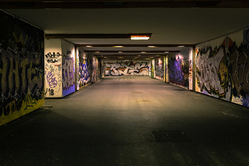 Croatia, Zagreb, June 21, the dark passage of a deserted, eerie creepy concrete indoor pathway grafted with graffiti at night