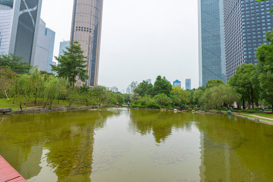 View of green tree and pond at Flower City Square with people walking and relaxing in Guangzhou, China