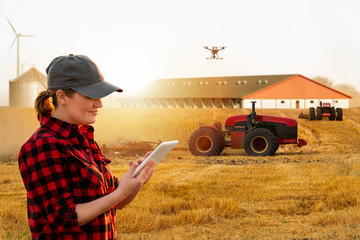 Wall Mural - Woman farmer with digital tablet controls an autonomous tractor and drone on a smart farm