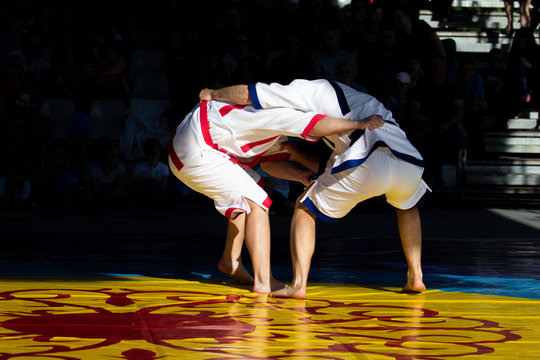 Two fighters Kuresh fighting on the mat. One athlete in red kureski and his opponent in blue kureski