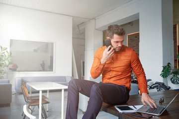 Businessman  using his mobile phone and talking with somebody while sitting at office desk