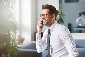 Businessman making a call while sitting in the office