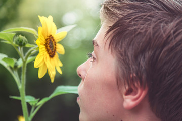 profile of a young man looking at a sunflower