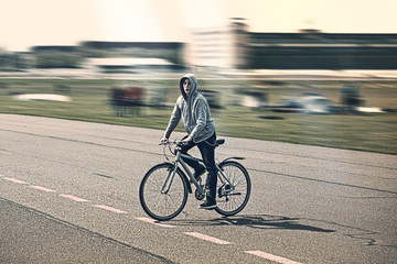 portrait of a young man rides a bicycle with blurred background
