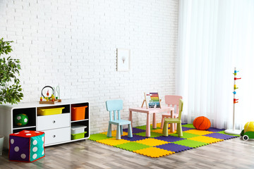 Stylish playroom interior with toys and modern furniture