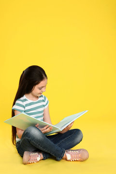 Cute little girl reading book on color background, space for text