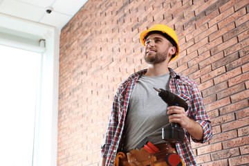 Young working man with screwdriver near brick wall. Space for text