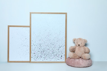 Adorable teddy bear and pictures on white background. Child room interior decor