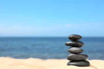 Stack of stones on sand near sea, space for text. Zen concept
