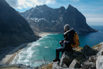 Man sitting on cliff edge alone enjoying aerial view backpacking lifestyle travel adventure outdoor vacations in Norway top of Reinebringen mountain. Wall mural