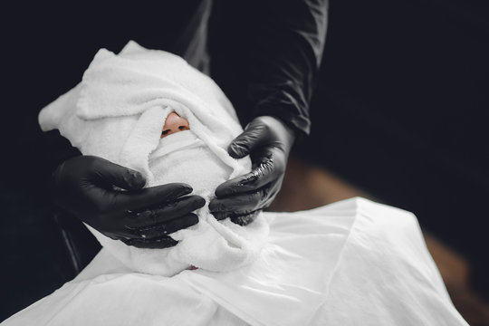 Man sits in barbershop chair and steam his face with hot towel in front of royal beard shaving razor