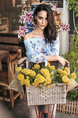 Poster Artist KB Brunette woman sitting on bike decorated with a bunch of flowers