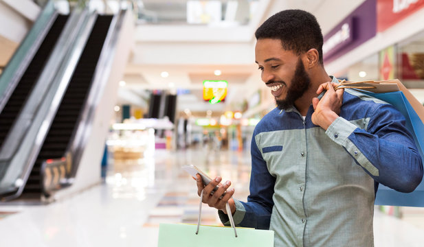 African american man with shopping bags using cellphone