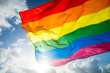 Close-up of gay pride rainbow flag fluttering backlit in bright sunny sky