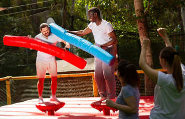 Fun wrestling with inflatable logs in an amusement park on a summer sunny day