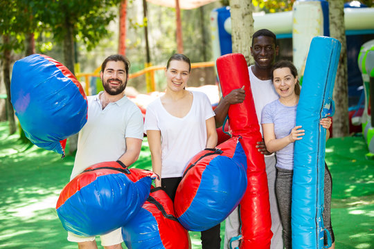 Portrait of happy friends with inflatable logs and pillows at an amusement park