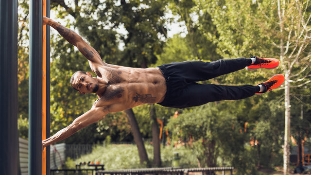 Strong Man Practicing Human Flag Exercise, Gripping Vertical Bar