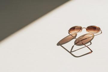 Modern women's sunglasses on white table. Modern minimal fashion blog hero header background.
