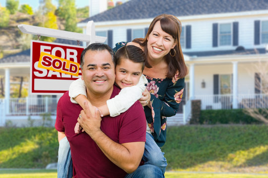 Happy Mixed Race Family In Front of House and Sold For Sale Real Estate Sign