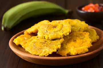 Patacon or toston fried and flattened pieces of green plantains, a traditional snack or accompaniment in the Caribbean (Selective Focus on the front of the top patacon)