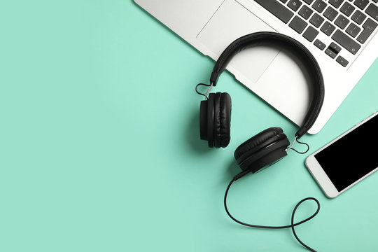 Modern headphones, phone and laptop on color background, flat lay. Space for text