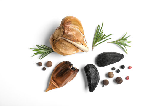 Aged black garlic with rosemary and peppercorns on white background, view from above