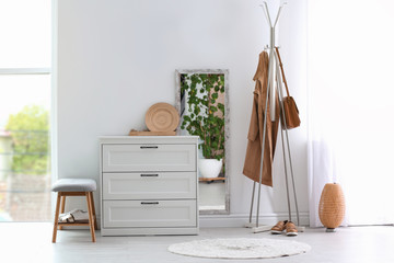Modern hallway interior with chest of drawers and clothes on hanger stand Fototapete