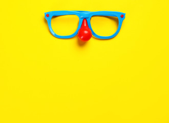 Masquerade glasses on colorful background, top view. Space for text