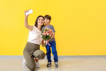 Happy mother and son taking selfie near color wall