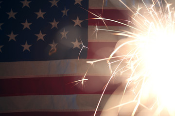 Wall Mural - Lit sparkler burning in front of American Flag
