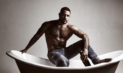 That means its bath time. Strong latino man with tattoo on muscular torso sitting in bath. Atheltic hispanic man drinking wine in bath. Wine and bath are the key to relaxation for him Wall mural