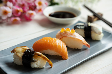 Close up of sashimi sushi set with soy sauce on white wooden table