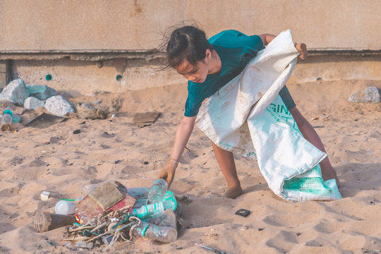 Children is picking up Plastic bottle and gabbage that they found on the beach for enviromental clean up concept