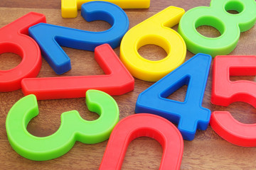 Many colorful plastic numbers on wooden table close up