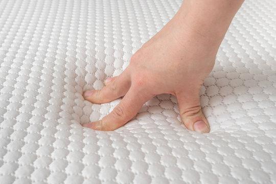 Woman is choosing new mattress for good sleeping