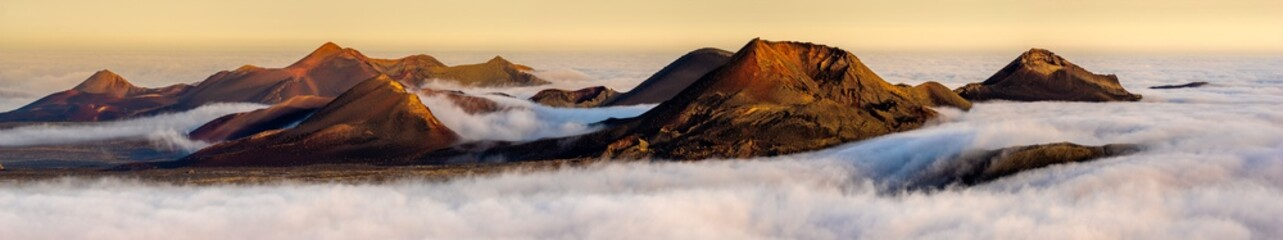 Poster Canarische Eilanden Volcanoes in the Timanfaya national park on Lanzarote. Volcanoes rising out of the clouds