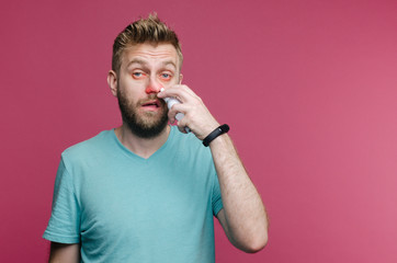 studio picture from a young man uses nose spray. Sick guy isolated has runny nose. man makes a cure for the common cold