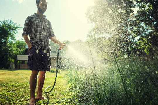 Hipster young man watering plants in a country house, summer and garden care