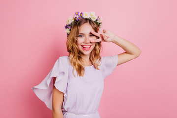 Wall Mural - Glad girl in cute wreath posing on bright background with peace sign. Indoor portrait of pleased curly woman with flower accessory having fun.