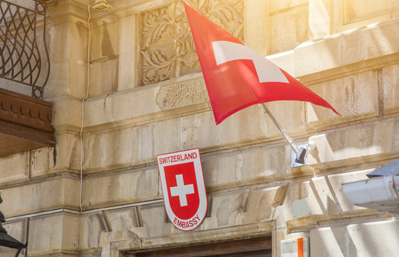 Switzerland national flags flying in the wind by a building in a city, square red flag with white cross