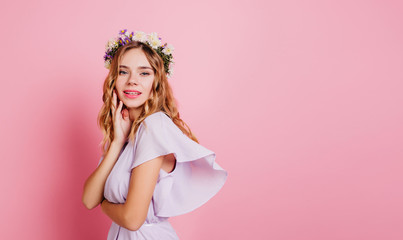 Wall Mural - Adorable caucasian woman with blonde hair posing with shy smile. Studio portrait of ecstatic white girl in flower wreath standing beside pink wall.
