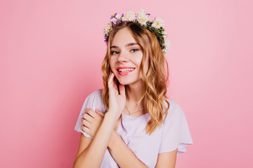 Wall Mural - Close-up portrait of good-looking white woman in circlet of flowers smiling to camera. Indoor photo of enchanting blonde girl in romantic attire.