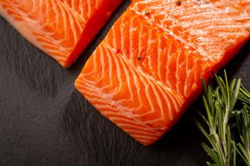 Salmon raw steak on slate with herbs