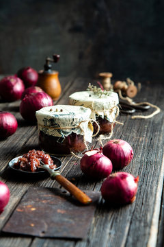 Homemade tasty canned onion red jam, marmalade, confiture, chutney in two glass jars on rustic wooden table