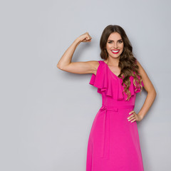 Strong Woman In Elegant Pink Dress Is Flexing Muscles And Smiling