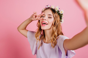 Wall Mural - Inspired fair-haired girl in purple attire spending time in studio. Close-up portrait of lovable blonde lady in flower wreath making selfie and laughing.
