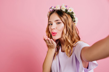 Wall Mural - Wonderful curly girl in circlet of flowers sending air kiss to camera. Fair-haired white lady making selfie on pink background.
