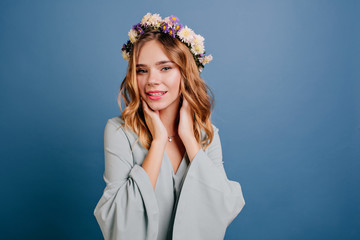 Wall Mural - Indoor portrait of carefree young woman with shiny blonde hair. Studio shot of magnificent white girl with flower wreath enjoying photoshoot.